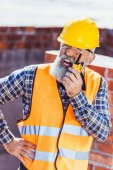 Fotografie Construction worker talking on portable radio