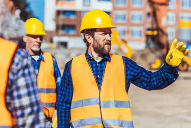 Builders discussing work while standing at construction site stock vector