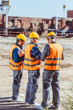 Three workers in hardhats and reflective vests standing at construction site stock vector