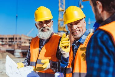 Two workers in reflective vests and hardhats examining building plans and talking on portable radio at construction site stock vector