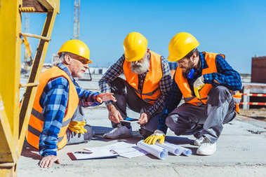 Three construction workers sitting on concrete at construction site, discussing building plans stock vector