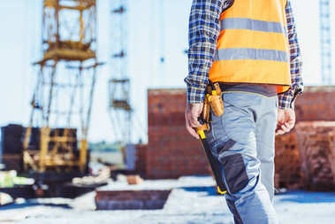 Cropped shot of builder in reflective vest standing at construction site stock vector