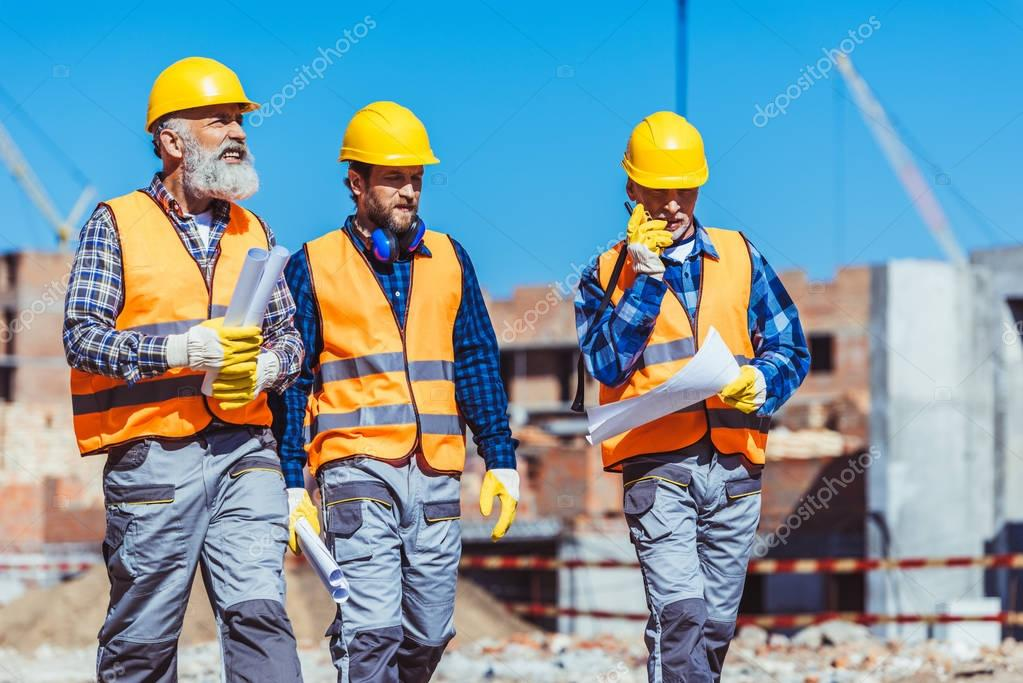 Three workers in reflective vests and hardhats walking together, with building plans and portable radio in their hands stock vector