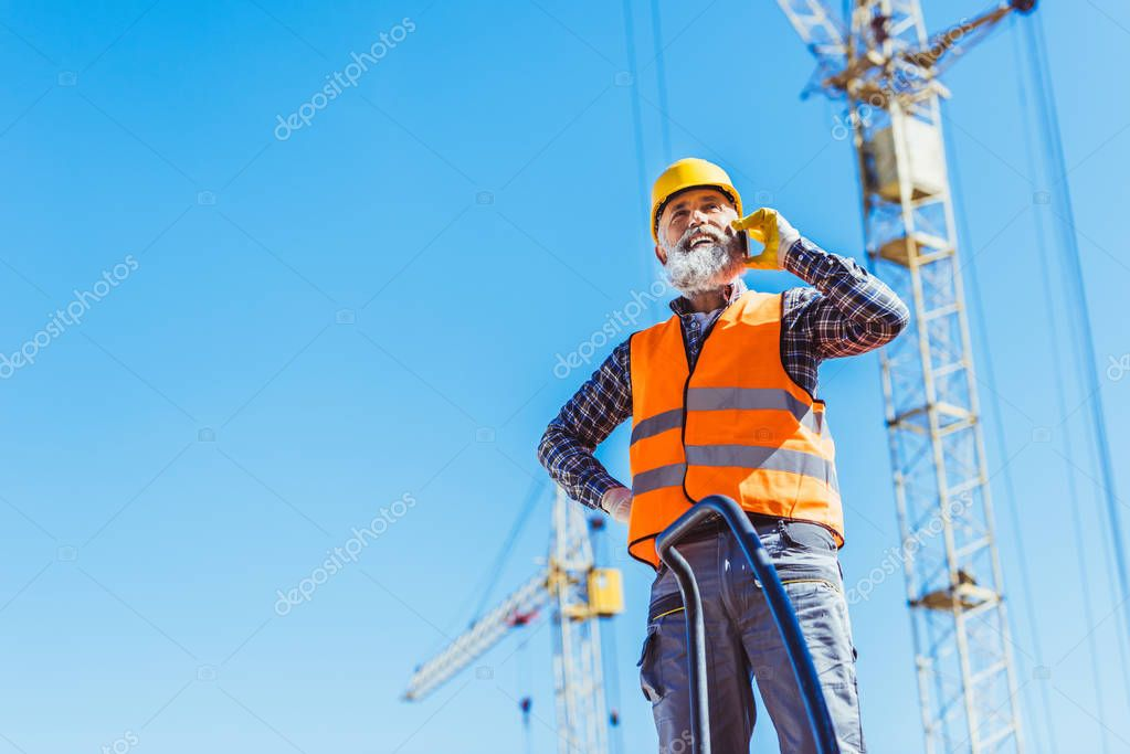 Smiling construction worker in reflective vest and hardhat talking on smartphone stock vector