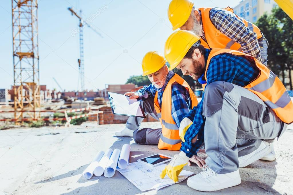 construction workers looking at building plans