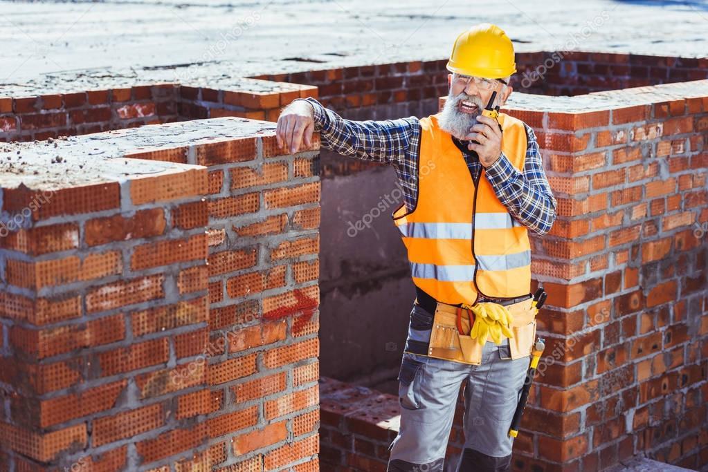 Construction worker talking on portable radio