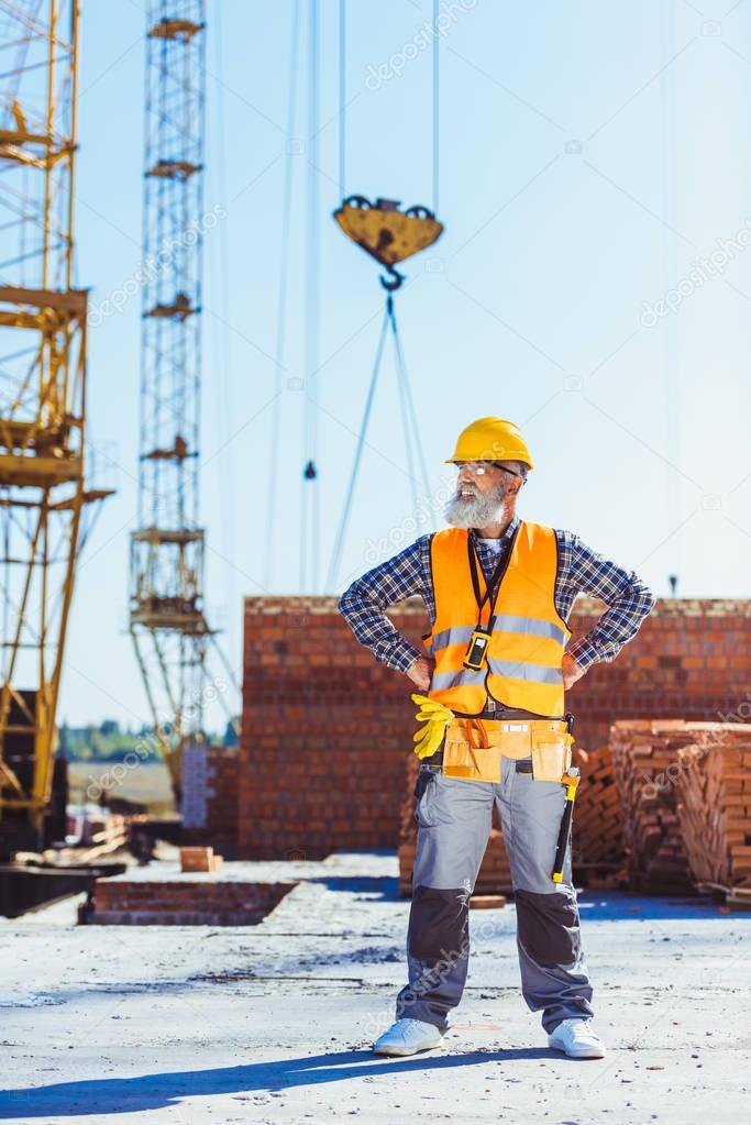 worker in uniform standing at construction site