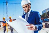 Podnikatel v přilba čtení stavební plány
