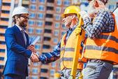 Fotografie Construction worker and businessman shaking hands