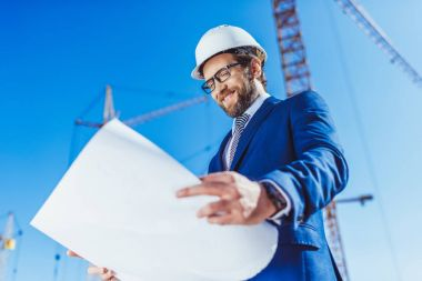 Businessman in hardhat examining building plans