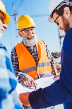Builders and businessman discussing construction plans