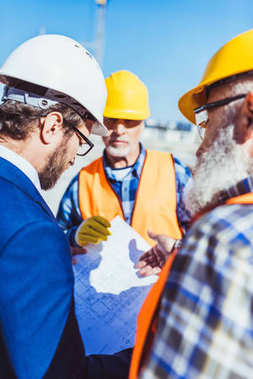 Workers in protective uniform discussing building plans with businessman at construction site stock vector