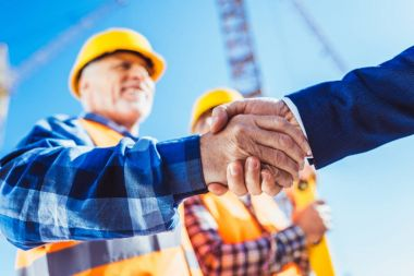 Construction worker in protective uniform shaking hands with businessman at construction site stock vector