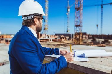 Businessman in hardhat and suit working with building plans at construction site stock vector