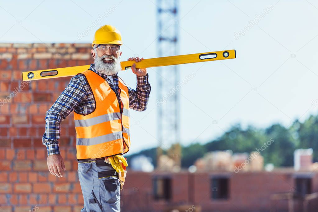 Smiling construction worker with spirit level