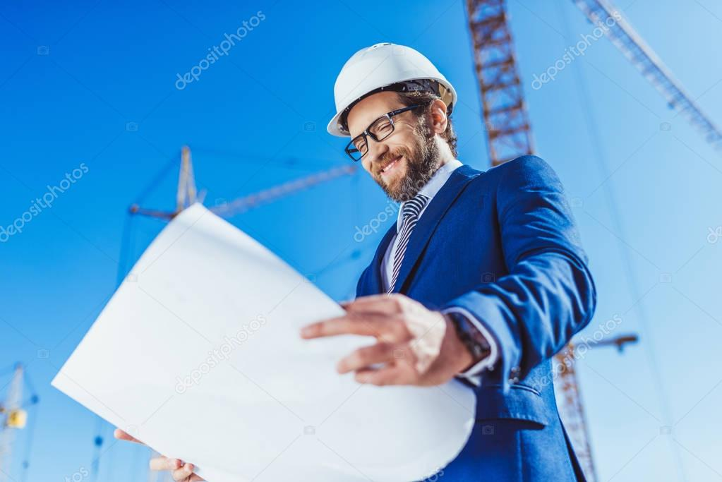 Businessman in hardhat examining building plans