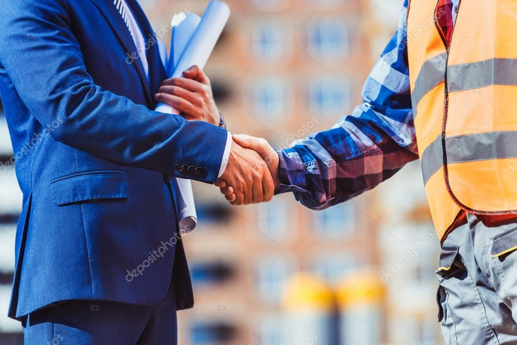Builder and businessman shaking hands
