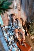 Fotografie Frau sitzt auf Bank in Holzhaus