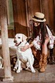 Fotografie Frau im Boho Stil Petting Hund