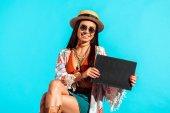 Hippie tourist holding black board