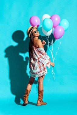 Hippie girl holding balloons