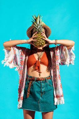 hippie woman covering face with pineapple