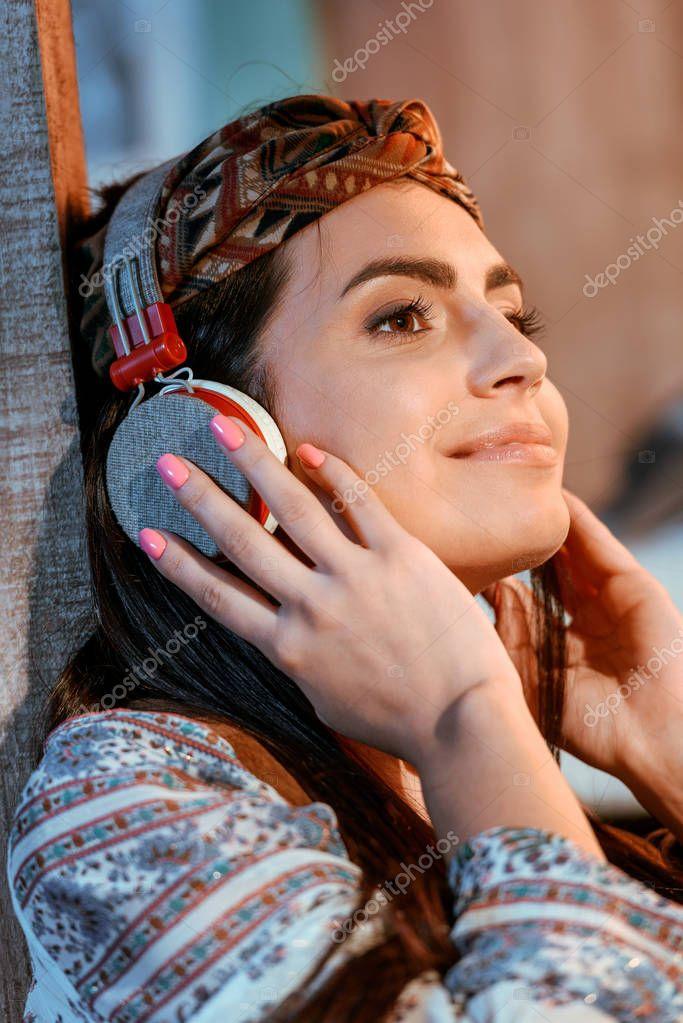 hippie girl listening to music in headphones