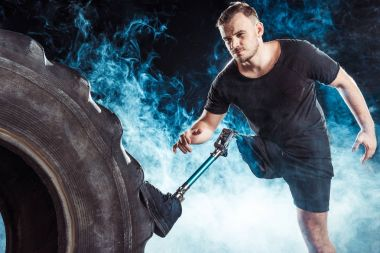 paralympic sportsman standing at tire
