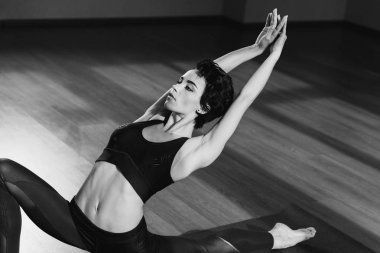 athletic woman stretching on yoga mat