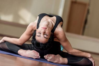 flexible woman sitting on yoga mat
