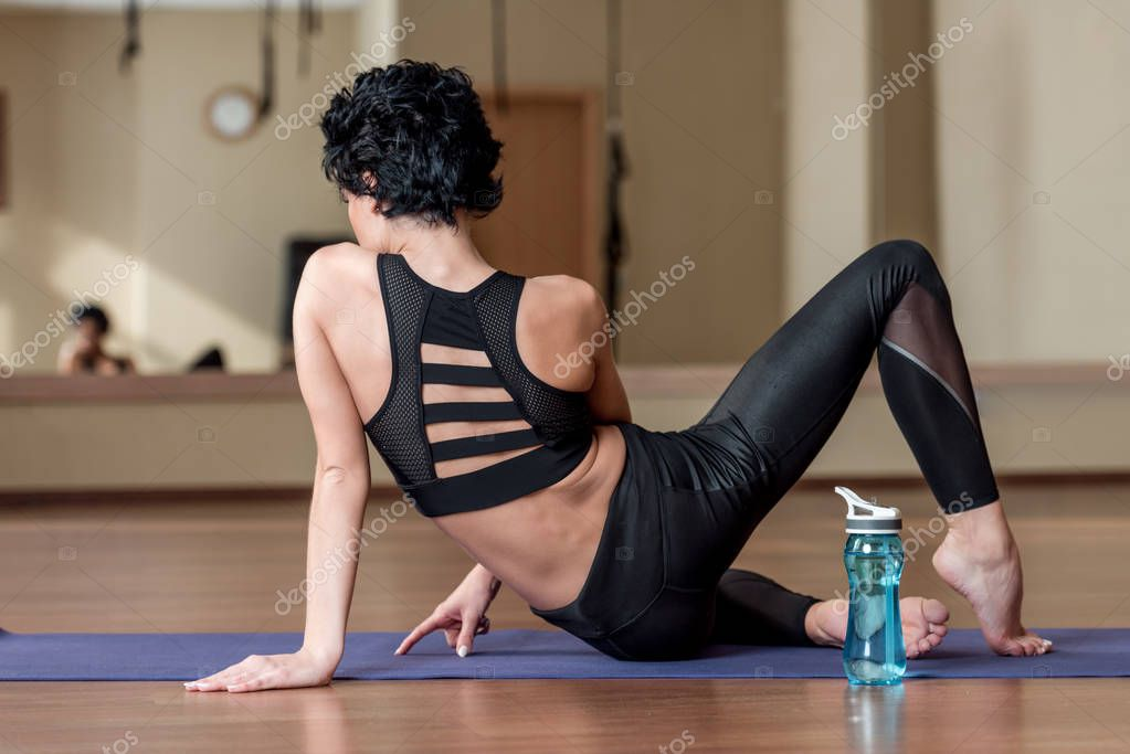woman relaxing on yoga mat