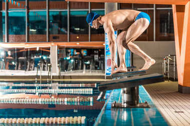 swimmer standing on diving board