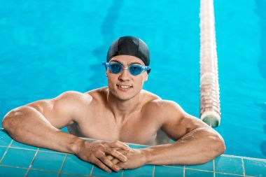 Handsome muscular swimmer in swimming cap and goggles in swimming pool stock vector