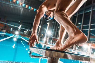 swimmer jumping into pool