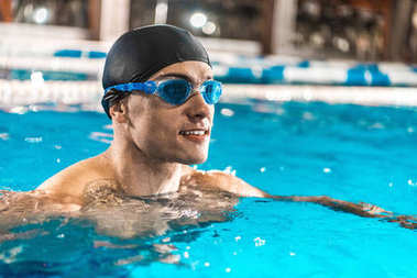 sportsman in goggles swimming in pool