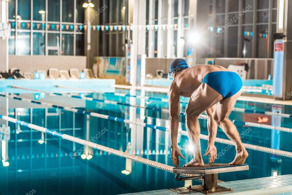 swimmer jumping into competition swimming pool