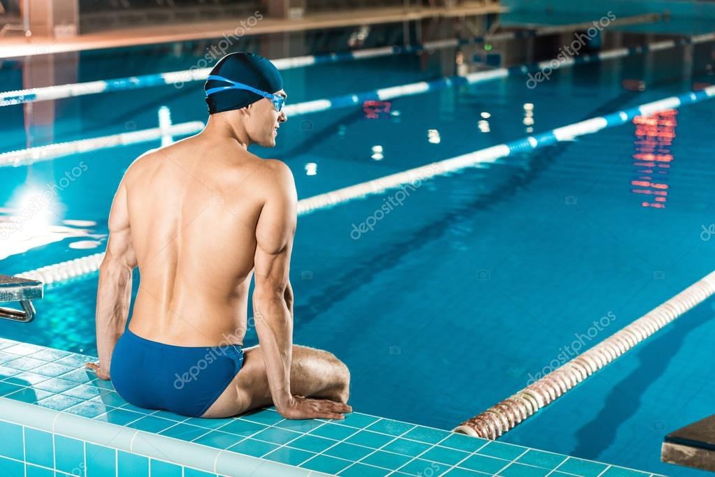 swimmer sitting at swimming pool