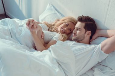 Young beautiful couple relaxing in bed at morning stock vector