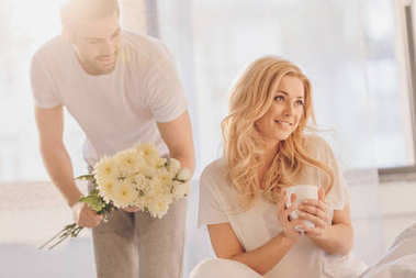 man presenting flowers for girlfriend