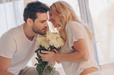man presenting flowers for girlfriend