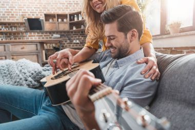couple playing guitar together