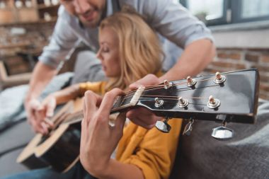 man learning girlfriend to play guitar