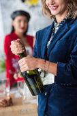 Fotografia bottiglia di champagne di apertura della donna