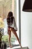 Fotografie verführerische Frau posiert auf der Fensterbank
