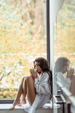 woman drinking coffee on windowsill
