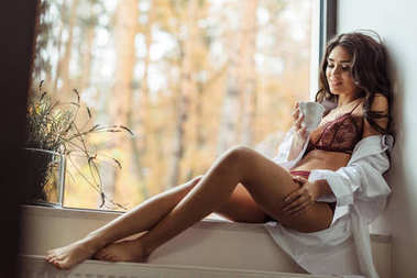girl in lingerie and white shirt on windowsill
