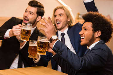 businessmen with beer watching soccer in bar