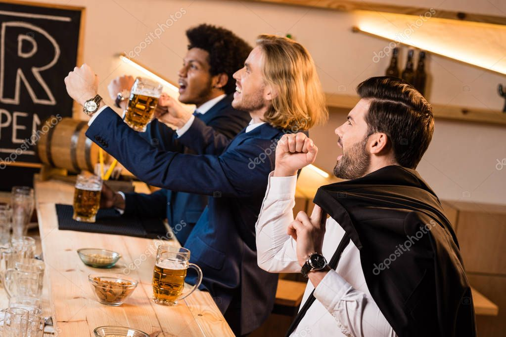 businessmen watching soccer game in bar