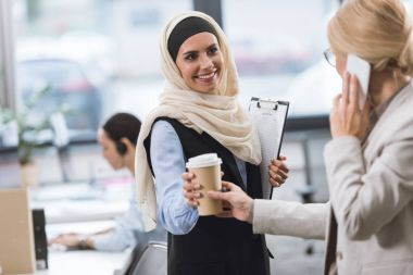 businesswoman giving coffee to colleague