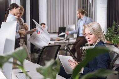 businesswoman in earphones with tablet